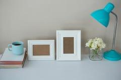 Cadres de tableau, tasse de café avec la lampe de table et vase à fleur Photos stock