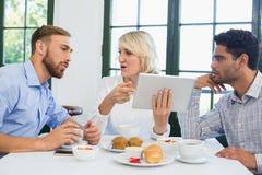 Cadres discutant au-dessus du comprimé numérique dans un restaurant Photographie stock libre de droits