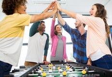 Cadres donnant la haute cinq tout en jouant le football de table Photos libres de droits