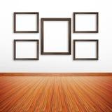 Cadres en bois de photo sur le mur blanc à l'intérieur de la salle Photographie stock libre de droits
