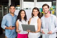 Cadres heureux tenant l'ordinateur portable, le comprimé numérique et le téléphone portable Photos stock