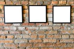 Cadres noirs vides vieux sur le vieux mur de briques Photographie stock