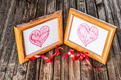 Cadres poussiéreux de photo avec des coeurs de dessin sur le fond en bois Photographie stock libre de droits