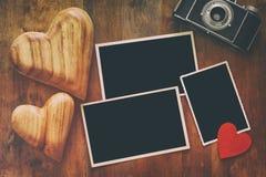 cadres vides de photo à côté de vieux appareil-photo et coeurs Images stock