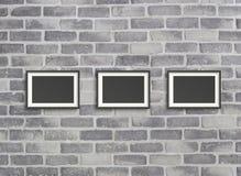 Cadres vides sur le mur gris de birck Images stock