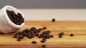 Caduta bianca della borsa dalla tavola lenta arrostita dell'arabica di caduta del primo piano del chicco di caffè stock footage