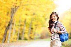 Caduta che fa un'escursione ragazza nella foresta di autunno Immagine Stock