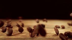 Caduta dei chicchi di caffè sulla tavola di legno archivi video