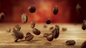 Caduta dei chicchi di caffè sulla tavola di legno stock footage