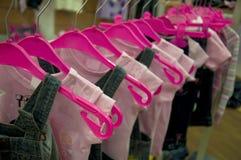 Caduta dei vestiti sui ganci in negozio Fotografia Stock