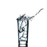 Caduta del cubetto di ghiaccio in bicchiere d'acqua a causa una spruzzata Fotografia Stock Libera da Diritti