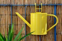 Caduta dell'annaffiatoio del metallo giallo sull'inferriata del balcone accanto alla pianta verde Fotografia Stock