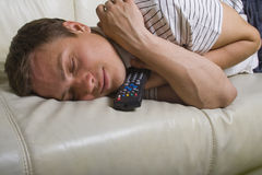 Caduta dell'uomo addormentata con telecomando della TV Fotografie Stock Libere da Diritti
