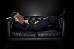 Caduta dell'uomo addormentata mentre leggendo Fotografie Stock