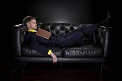 Caduta dell'uomo addormentata mentre leggendo Fotografie Stock Libere da Diritti