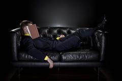 Caduta dell'uomo addormentata mentre leggendo Fotografia Stock