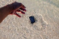 Caduta della macchina fotografica del telefono all'acqua di mare vicino alla spiaggia Fotografie Stock