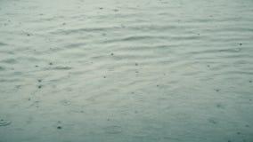 Caduta delle gocce di pioggia sulla superficie dell'acqua archivi video