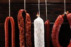 Caduta delle salsiccie da uno scaffale al mercato Stile di buio del paese Traditi fotografia stock libera da diritti