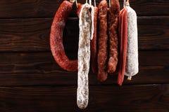 Caduta delle salsiccie da uno scaffale al mercato Stile di buio del paese Traditi immagini stock