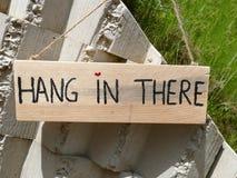 Caduta di legno del segno là nell'attaccatura sulla parete di pietra con cuore come fanno Immagine Stock