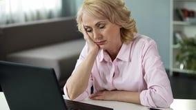 Caduta matura della donna addormentata al posto di lavoro, alla mancanza di vitamine ed all'energia, stanchi immagine stock