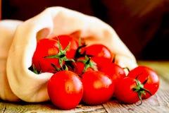 Caduta matura rossa dei pomodori dal sacco Vista rustica Fotografie Stock Libere da Diritti
