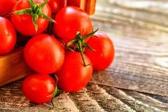 Caduta matura rossa dei pomodori dalla scatola Vista rustica Immagini Stock