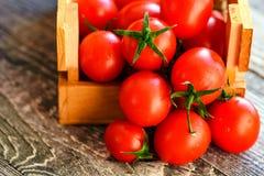 Caduta matura rossa dei pomodori dalla scatola Vista rustica Immagine Stock