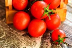 Caduta matura rossa dei pomodori dalla scatola Vista rustica Fotografia Stock