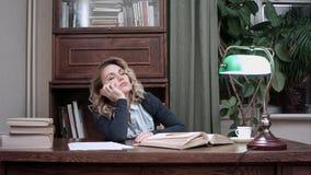 Caduta stanca della giovane donna addormentata sopra un libro mentre sedendosi alla tavola Fotografia Stock