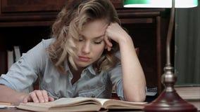 Caduta stanca della giovane donna addormentata sopra un libro mentre sedendosi alla tavola dopo il giorno lungo di lavoro Immagine Stock Libera da Diritti