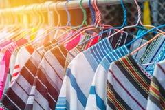 Caduta variopinta di modo dei vestiti su uno scaffale ad acquisto del mercato delle pulci Fotografia Stock Libera da Diritti