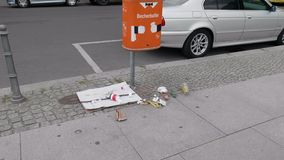 Cadute dei rifiuti dalla pattumiera riempita troppo ad una via della città di Berlino - colpo giunto cardanico/del carrello - 4K stock footage