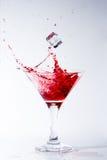 Cadute di ghiaccio in un vetro con il cocktail rosso Fotografia Stock Libera da Diritti