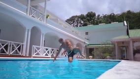 Cadute di posa divertenti del giovane nella piscina stock footage