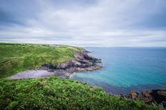 Caerfai Beach footpath area seascape view on a cloudy day West Wales UK.  Royalty Free Stock Photos