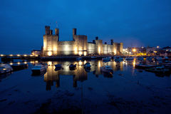 Caernarfon Castle. In the blue hour just after dusk at high tide north wales UK Stock Images