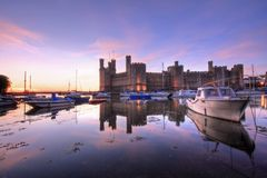 Caernarfon castle. And battlements along the River Seiont in North Wales Stock Photo