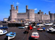 Caernarfon Castle and harbour. View of the medieval castle fortress with fishing boats in the foreground, Caernarfon, Gwynedd, Wales, UK, Western Europe Stock Photography