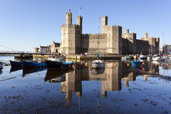 Caernarfon Castle, North Wales. Castle and moored boats at harbor of Caernarfon, North Wales Stock Photo