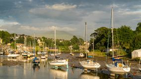 Caernarfon, Gwynedd, Wales, UK. June 15, 2017: Evening sun over boats at the shore of Afon Seiont with clouds over Snowdonia in the background Royalty Free Stock Image