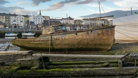 Caernarfon, Gwynedd, Wales, UK. June 15, 2017: Old dirty boat at the shore of Afon Seiont with new boats and some houses in the background Stock Photos