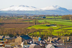 Caernarfon, Wales. Town of Caernarfon and snow covered Snowdonian mountains, Wales, UK royalty free stock image