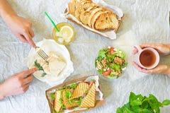 Caesar sałatki, bruschetta, baleronu i pomidoru kanapek stół z rękami, odgórny widok z góry zdjęcia stock