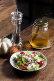 Caesar salad with bacon, cheese and tomato. With beverage on wood table Royalty Free Stock Image