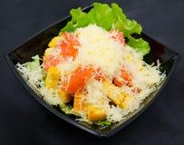 Caesar salad in black bowl Stock Photo