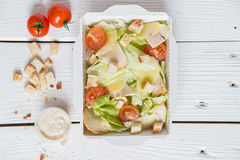 Caesar salad in box on white wooden surface Stock Images