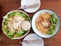 Caesar salad and carbonara on a wooden table. Caesar salad and carbonara pasta on a wooden table Royalty Free Stock Photos