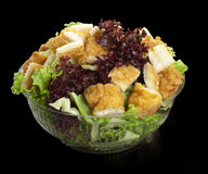 Caesar salad with chicken and lettuce. Salad with chicken and fresh lettuce on black background in transparent bowl royalty free stock photography